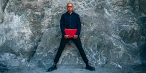 Man som håller i ett rött datorfodral i läder