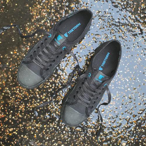 Ett par svarta sneakers i regn
